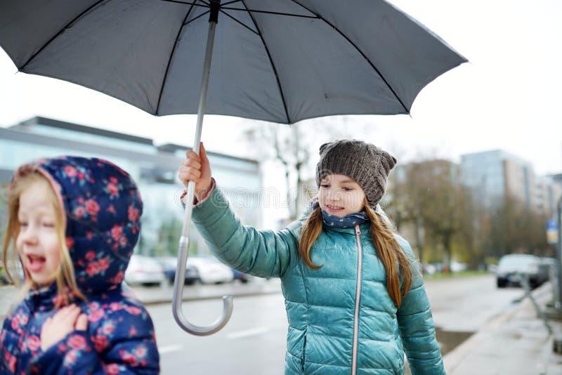 Två gulliga lilla systrar som går under paraplyet arkivfoto