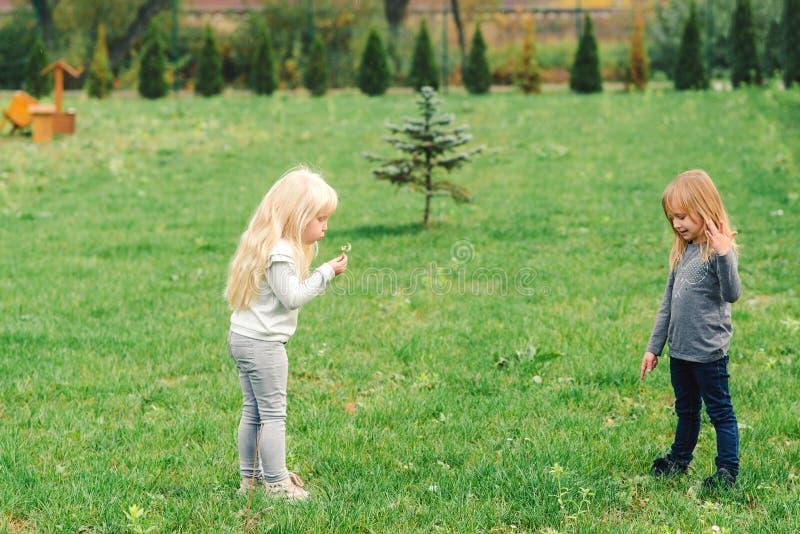 Två gulliga lilla systrar som har gyckel i trädgård Lyckliga ungar som utomhus spelar Natur och utomhus gyckel för familj lycklig royaltyfri fotografi