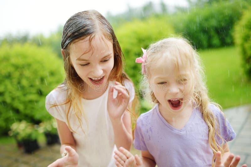 Två gulliga lilla systrar som har gyckel under varmt sommarregn arkivfoton