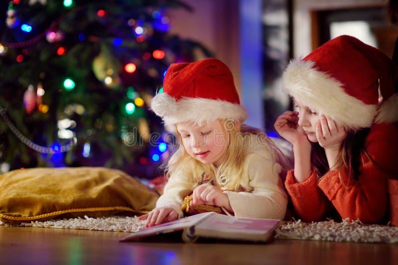 Två gulliga lilla systrar som läser en berättelse, bokar tillsammans under en julgran arkivfoton