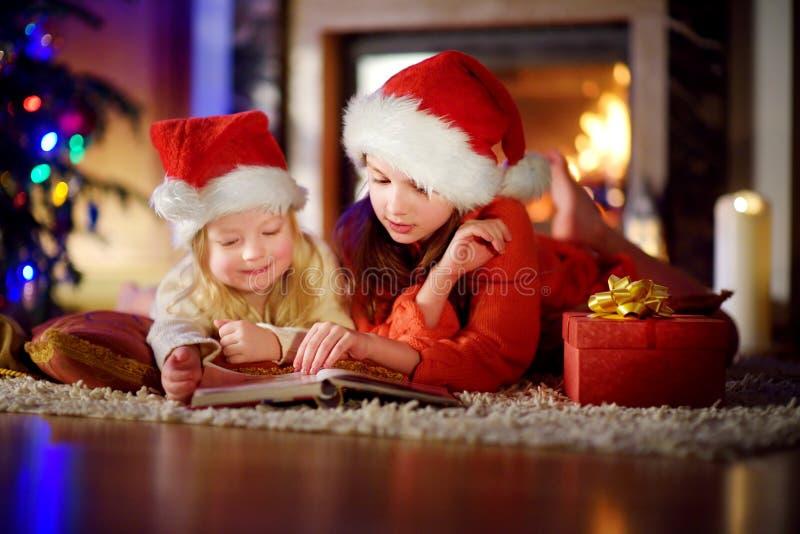 Två gulliga lilla systrar som läser en berättelse, bokar tillsammans under en julgran royaltyfri fotografi