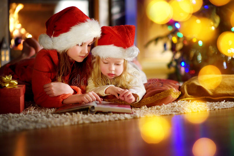 Två gulliga lilla systrar som läser en berättelse, bokar tillsammans under en julgran royaltyfria foton