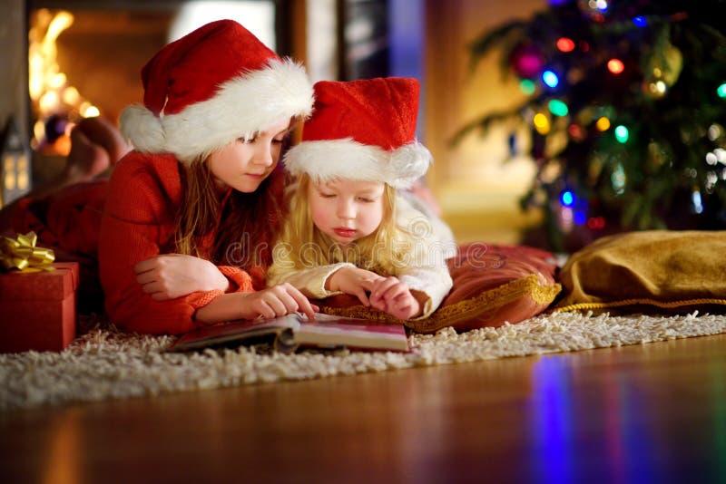 Två gulliga lilla systrar som läser en berättelse, bokar tillsammans under en julgran arkivbild