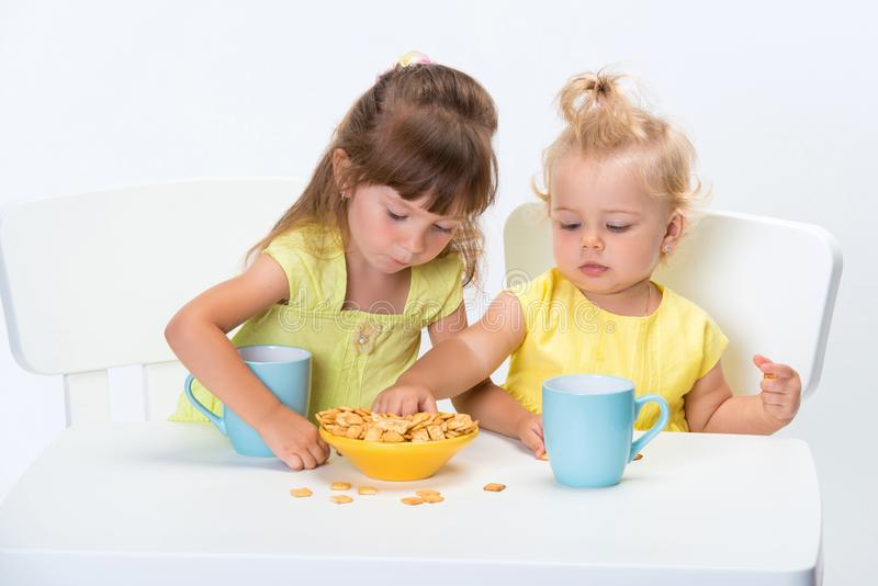 Två gulliga liten flickasystrar som äter sädes- flingor och dricker en kopp av, mjölkar eller te på tabellen som isoleras på vit  arkivbilder