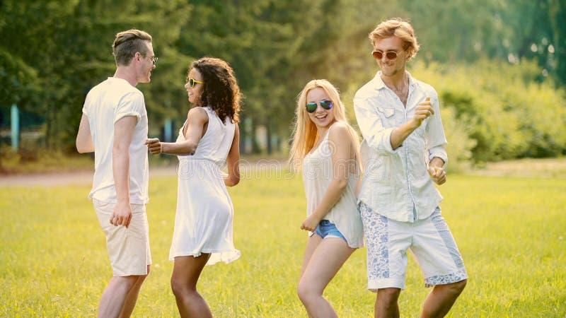 Två gulliga par som ut hänger på den frilufts- festivalen och att dansa till musik och att ha gyckel arkivfoton