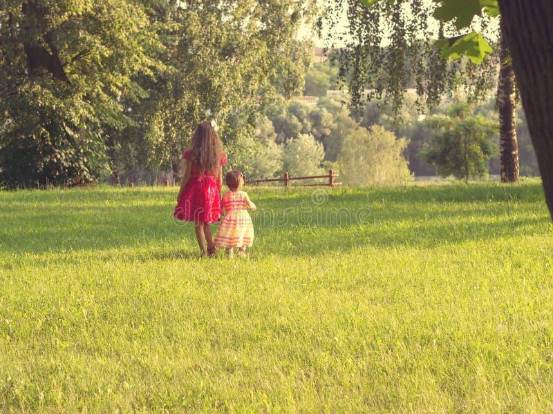 Två gulliga små flickor i härliga klänningar som har gyckel på solnedgången tonat arkivfoton
