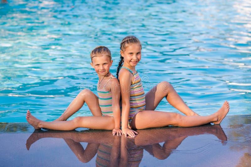 Två gulliga små flickor i simbassäng royaltyfri fotografi