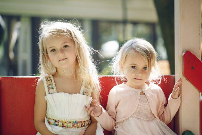 Två gulliga små flickor som har gyckel på en lekplats utomhus i sommar royaltyfri bild