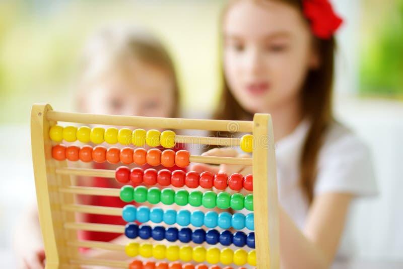 Två gulliga små flickor som spelar med den hemmastadda kulrammet Storasyster som undervisar hennes sibling att räkna Smart barn s royaltyfri fotografi