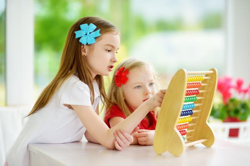 Två gulliga små flickor som spelar med den hemmastadda kulrammet Storasyster som undervisar hennes sibling att räkna Smart barn s arkivbild