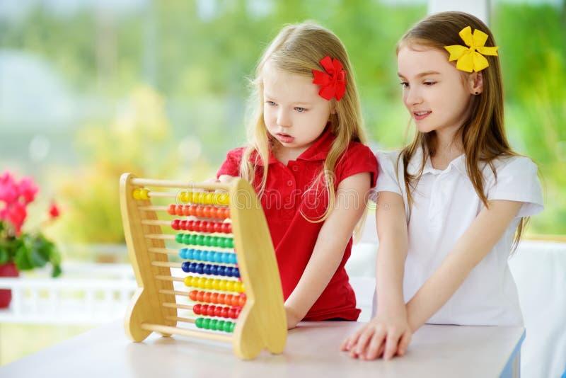Två gulliga små flickor som spelar med den hemmastadda kulrammet Storasyster som undervisar hennes sibling att räkna Smart barn s royaltyfri foto