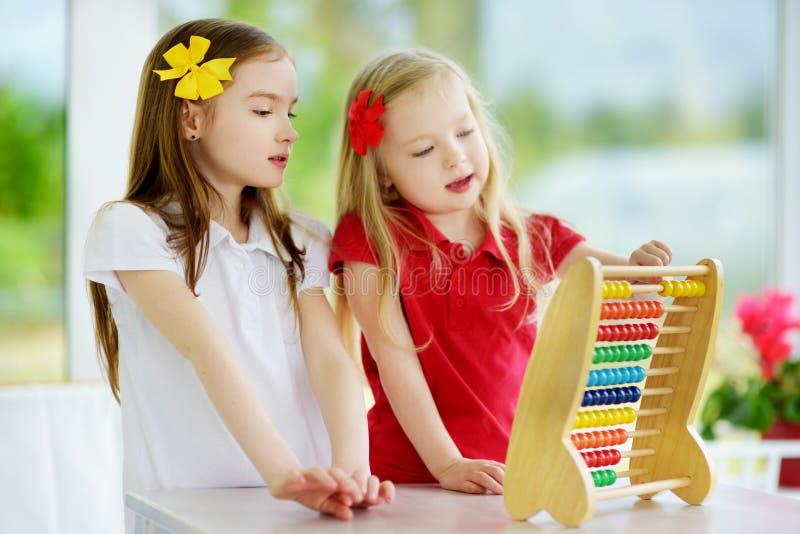 Två gulliga små flickor som spelar med den hemmastadda kulrammet Storasyster som undervisar hennes sibling att räkna Smart barn s arkivfoton