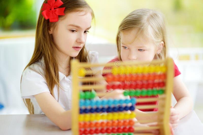 Två gulliga små flickor som spelar med den hemmastadda kulrammet Storasyster som undervisar hennes sibling att räkna Smart barn s arkivbilder