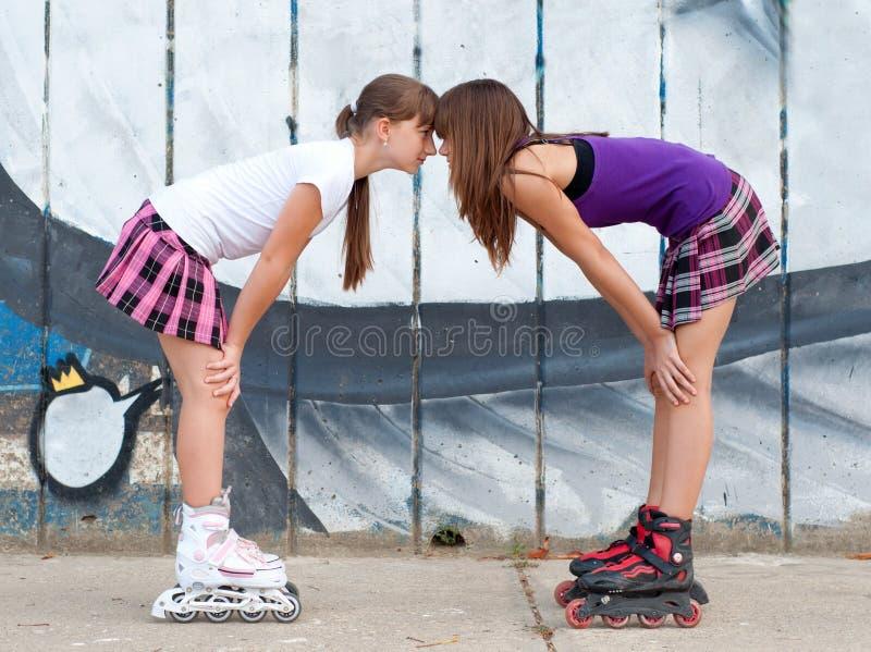 Två gulliga tonårs- flickor på rullskridskor som har gyckel arkivbild
