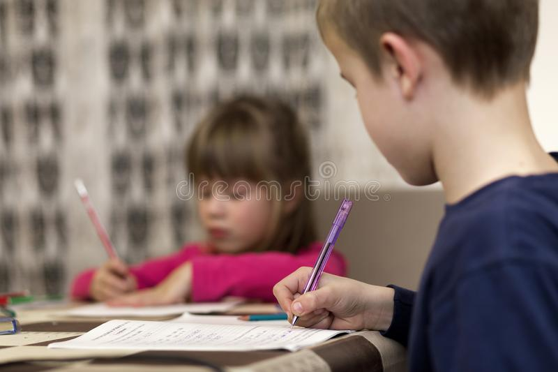 Två gulliga unga barn, pojke och flicka, syskongrupp som gör läxa, hemma skriver och drar på suddig bakgrund konst arkivbilder