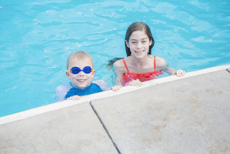 Två gulliga ungar som spelar i en simbassäng på en solig dag royaltyfri bild