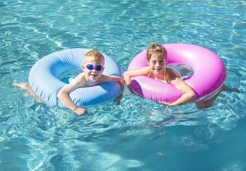 Två gulliga ungar som spelar på uppblåsbara rör i en simbassäng på en solig dag fotografering för bildbyråer