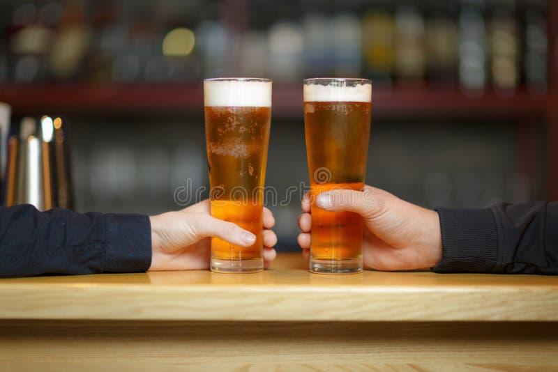 Två händer för man` s rymmer två exponeringsglas med ett öl arkivbilder