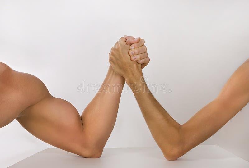 Två händer knäppte fast den svag armbrottningen (som var stark och), olika match royaltyfri foto