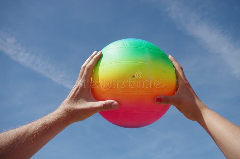 Två händer med bollen på strandteamwork arkivfoton