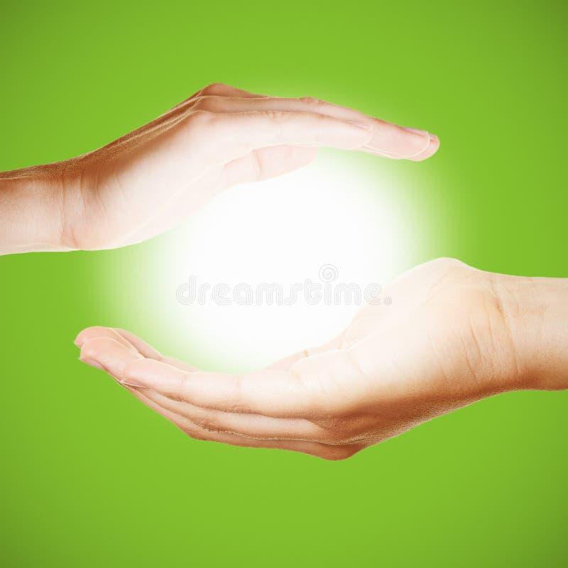 Två händer rymmer ett glödande ljus eller sol royaltyfri foto