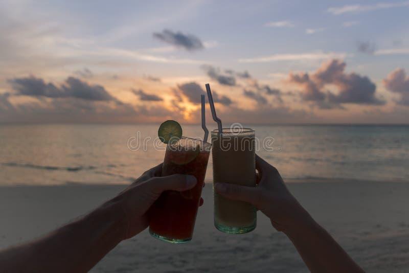 Två händer som klirrar coctailar under en solnedgång på stranden tropisk semester f?r ? Lycklig timme fotografering för bildbyråer