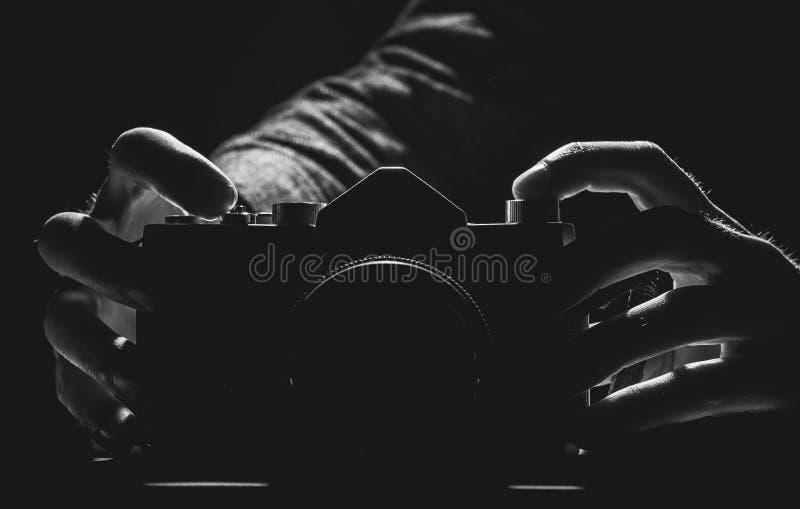 Två händer som rymmer en gömd kamera i svartvitt royaltyfri foto