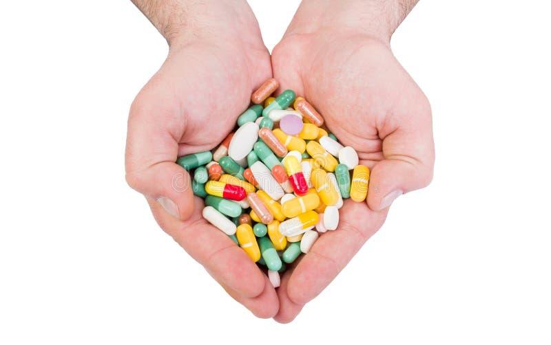 Två händer som rymmer många preventivpillerar royaltyfria foton