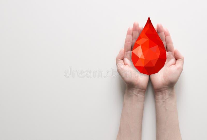 Två händer som rymmer röd polygonal bloddroppe arkivfoton