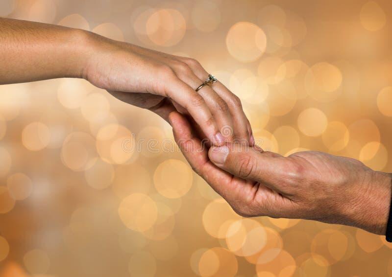 Två händer som rymmer sig med mousserande ljus bokehbakgrund royaltyfri foto