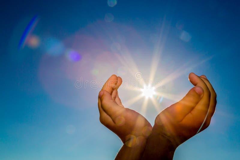 Två händer som rymmer solen på en bakgrund för blå himmel arkivbild