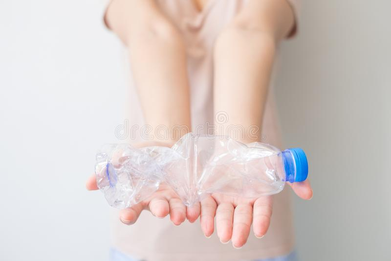 Två händer som vrider den klara plast- flaskan på isolerad vit bakgrund och inklusive urklippbanan, Resize den plast- flaskan för arkivfoto