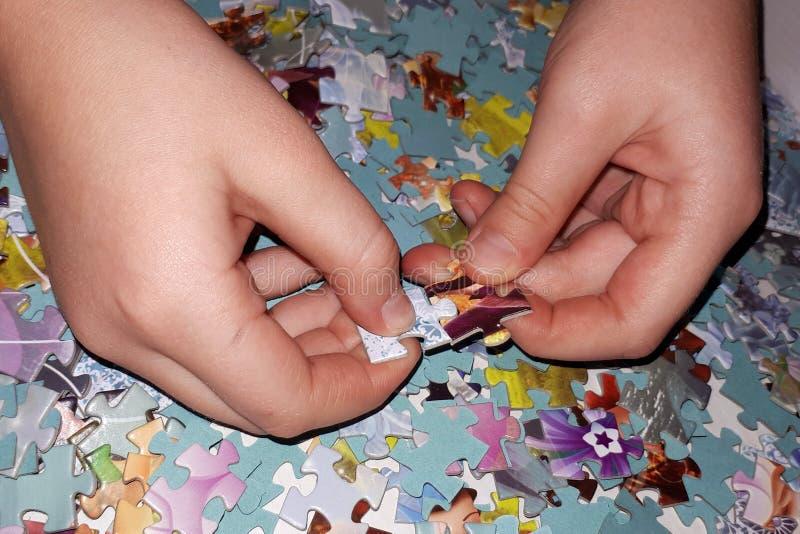 Två händer väljer upp pussel royaltyfri bild