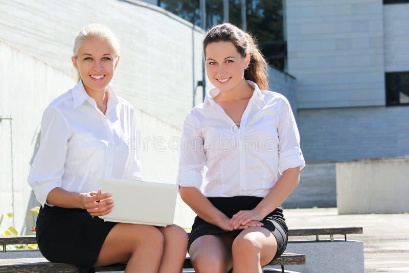 Två härliga affärskvinnor som sitter med bärbara datorn över gatabac royaltyfri foto