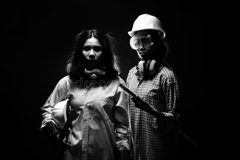Två härliga asiatiska arkitektEngineer kvinnor i den hårda hatten, protec royaltyfri bild