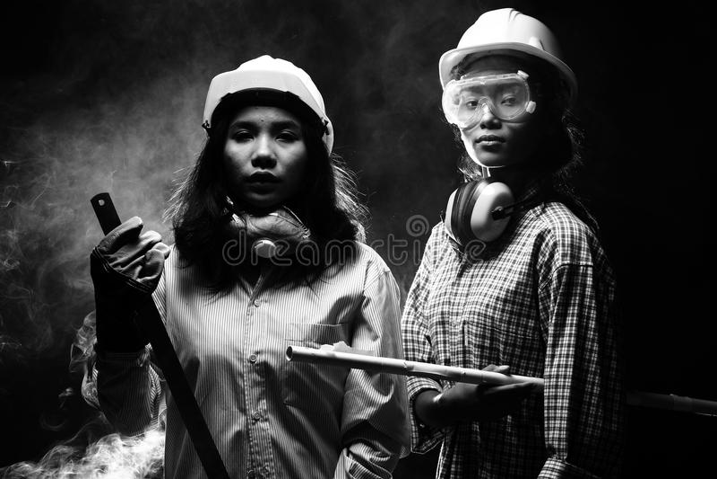 Två härliga asiatiska arkitektEngineer kvinnor i den hårda hatten, protec royaltyfri fotografi