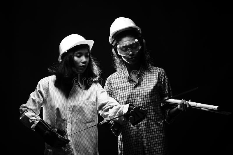 Två härliga asiatiska arkitektEngineer kvinnor i den hårda hatten, protec arkivfoto