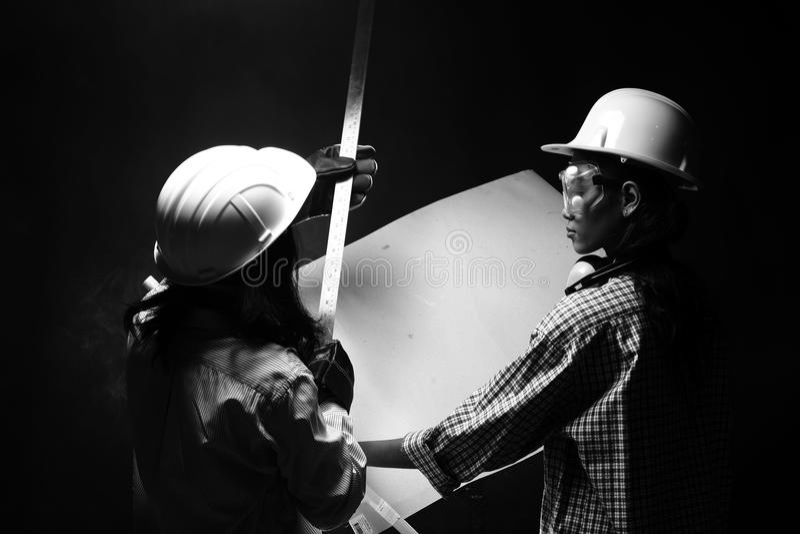 Två härliga asiatiska arkitektEngineer kvinnor i den hårda hatten, protec royaltyfria bilder