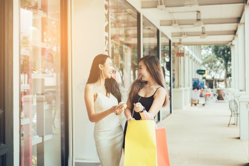 Två härliga asiatiska kvinnliga vänner tycker om shopping med innehavpapperspåsen royaltyfri fotografi