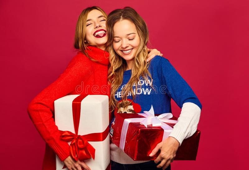 Två härliga blonda flickor som poserar på röd bakgrund royaltyfri fotografi