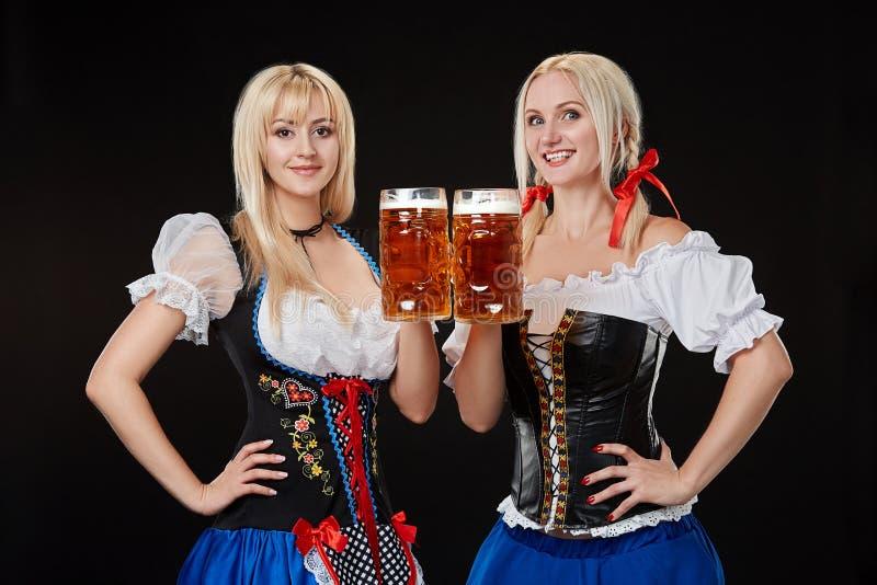 Två härliga blonda kvinnor är hållande exponeringsglas av öl i händer och står på svart bakgrund i studio fotografering för bildbyråer