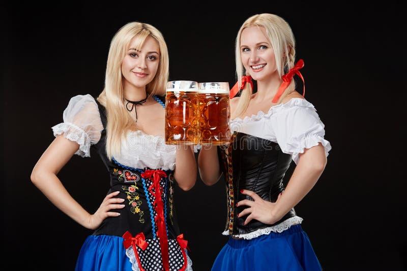 Två härliga blonda kvinnor är hållande exponeringsglas av öl i händer och står på svart bakgrund i studio arkivbild