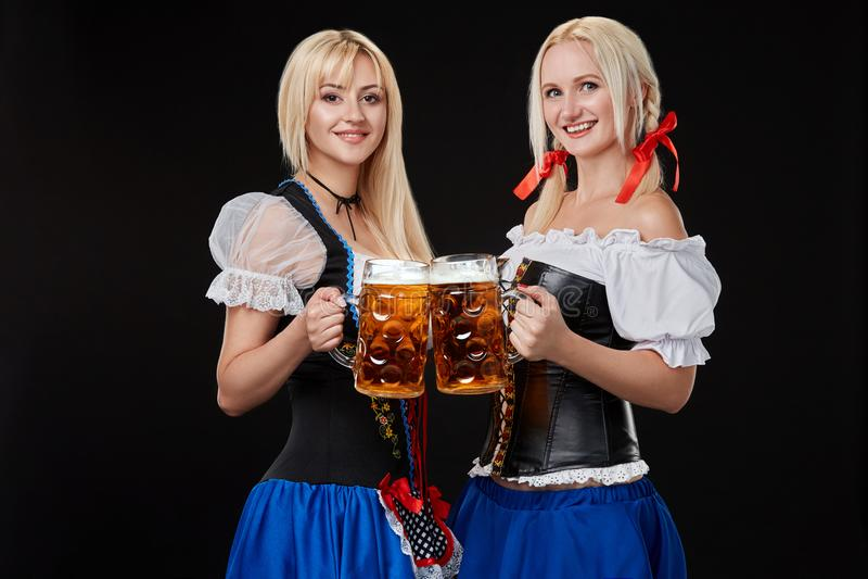 Två härliga blonda kvinnor är hållande exponeringsglas av öl i händer och står på svart bakgrund i studio royaltyfri fotografi