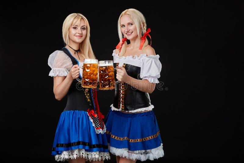 Två härliga blonda kvinnor är hållande exponeringsglas av öl i händer och står på svart bakgrund i studio arkivfoto