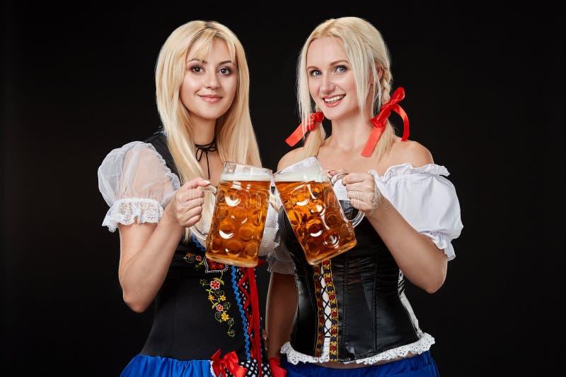 Två härliga blonda kvinnor är hållande exponeringsglas av öl i händer och står på svart bakgrund i studio arkivfoton