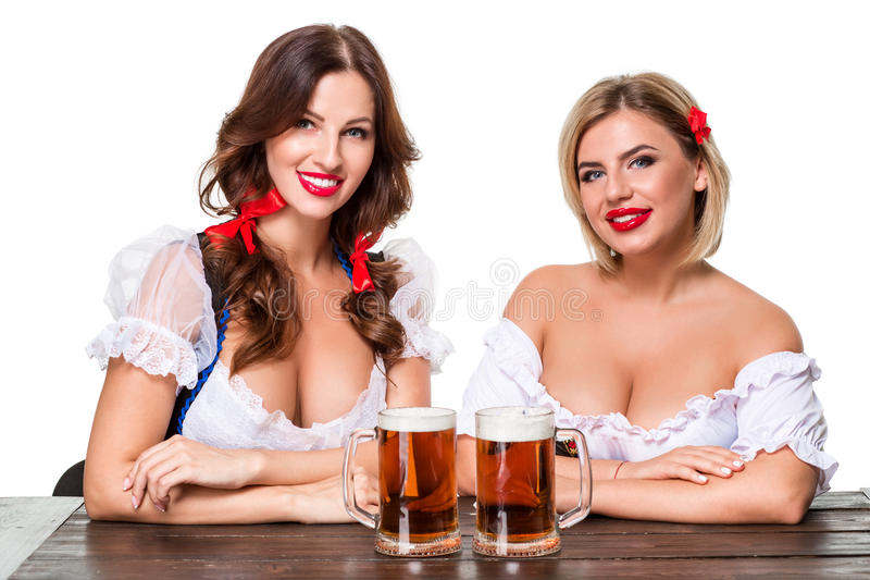 Två härliga blonda och brunettflickor av den mest oktoberfest ölölkruset arkivfoton