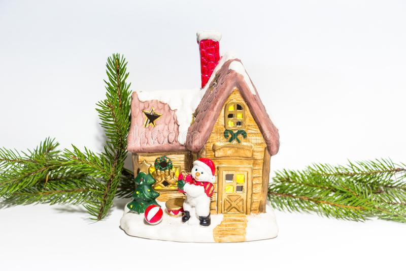 Två härliga dekorerat nytt års hus står på en vit bakgrund, bredvid ett hus är en snögubbe Runt om husen är gran b royaltyfri foto