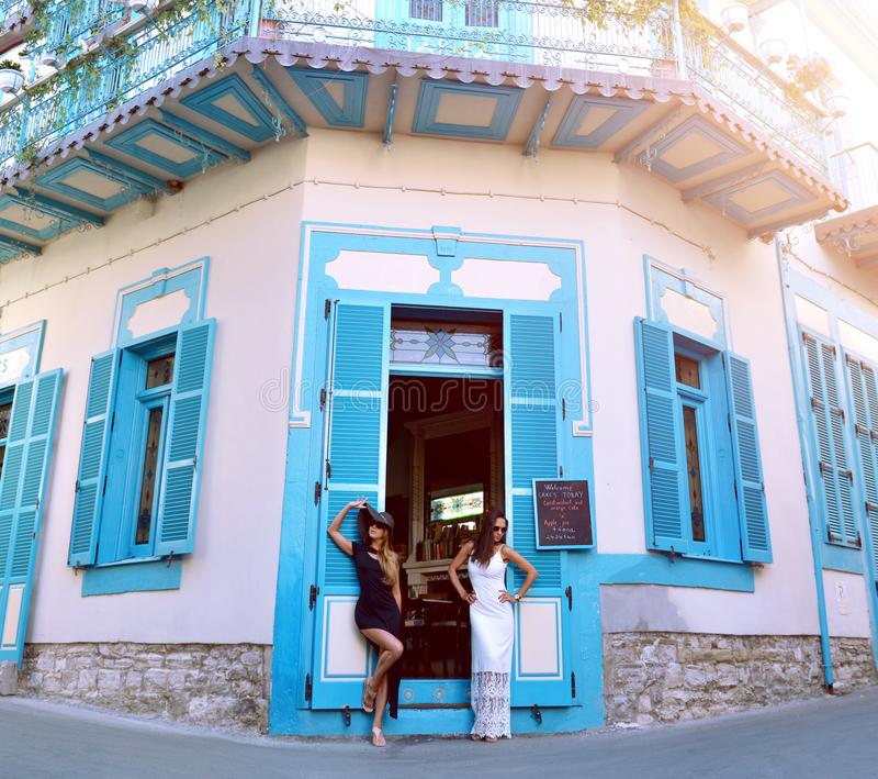 Två härliga flickavänner som står nära det berömda bykafét i Lefkara, Cypern Stället av folk tillverkar det nationella arvet royaltyfria bilder