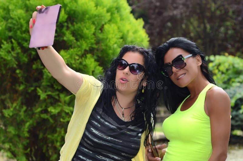 Två härliga flickor gör selfi fotografering för bildbyråer