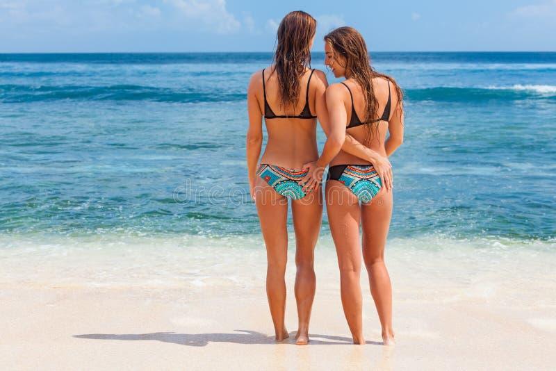 Två härliga flickor i bikini på vit sand sätter på land arkivfoton